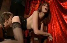 Dominatrix in black stockings having fun with her slave